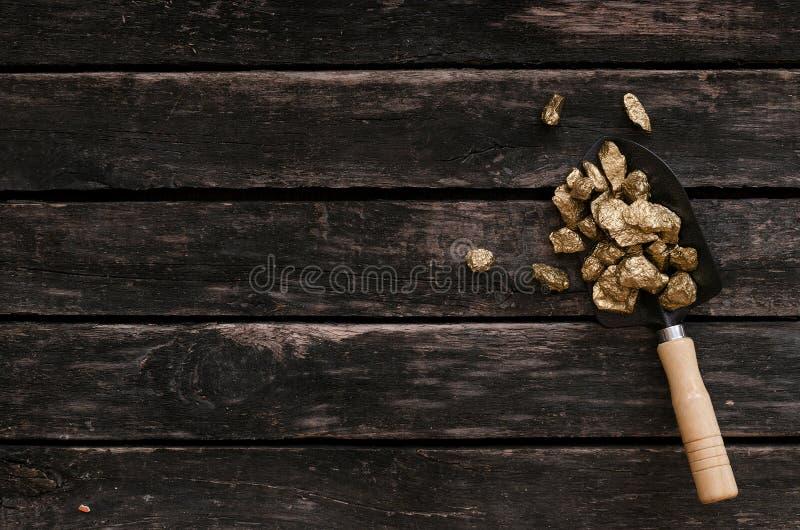 Gold ore in a shovel. Treasure hunter. Adventurer. Gold ore nuggets in shovel on old adventurer table. Goldminer Treasure hunter concept royalty free stock images