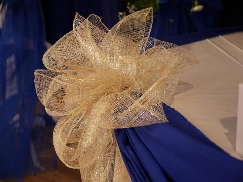 Wedding floral arrangement. Gold organza ribbon used as centerpiece decoration for a wedding stock photography