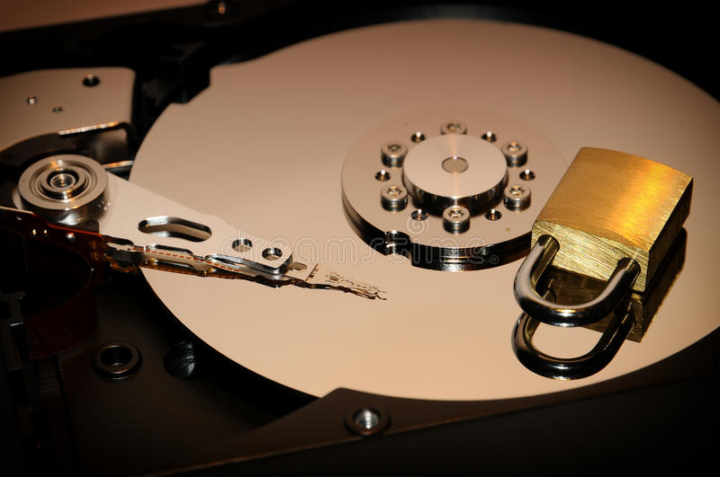 Gold padlock on the opened HDD disk drive surface. Data protection or security concept. Security background stock image