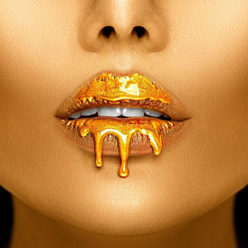 Gold paint drips from the lips, golden liquid drops on beautiful model girl`s mouth, creative abstract makeup. Beauty woman face stock photo