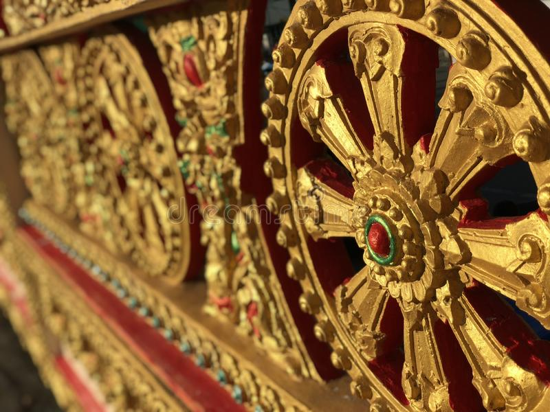 Gold-painted wall fence Thai Buddhist temple under the rays of the soft evening sun stock photo