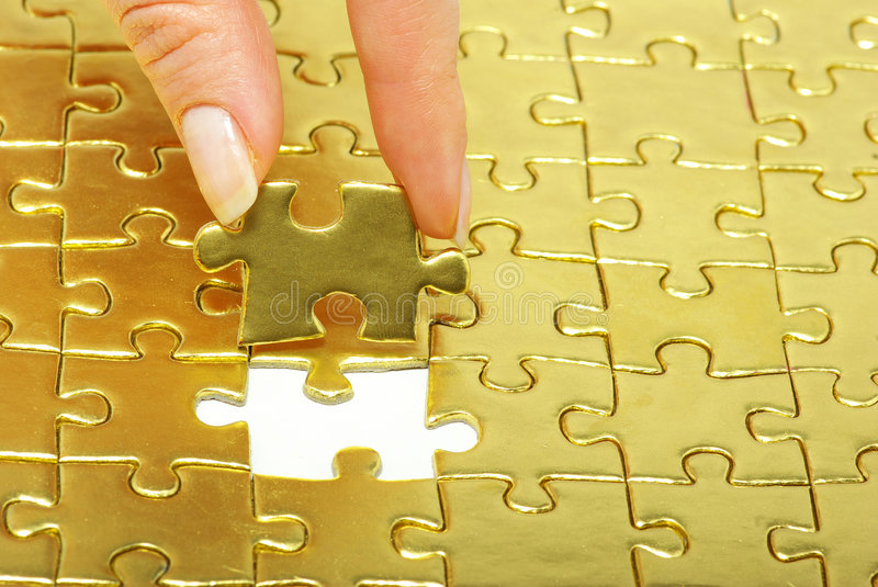 Gold pazles. Woman fingers holdings gold pazles stock photography
