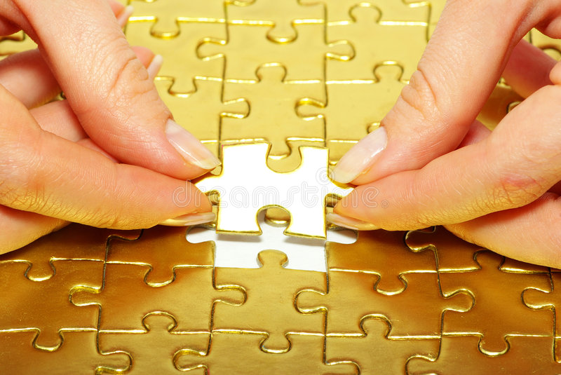 Gold pazles. Woman fingers holdings gold pazles royalty free stock photo