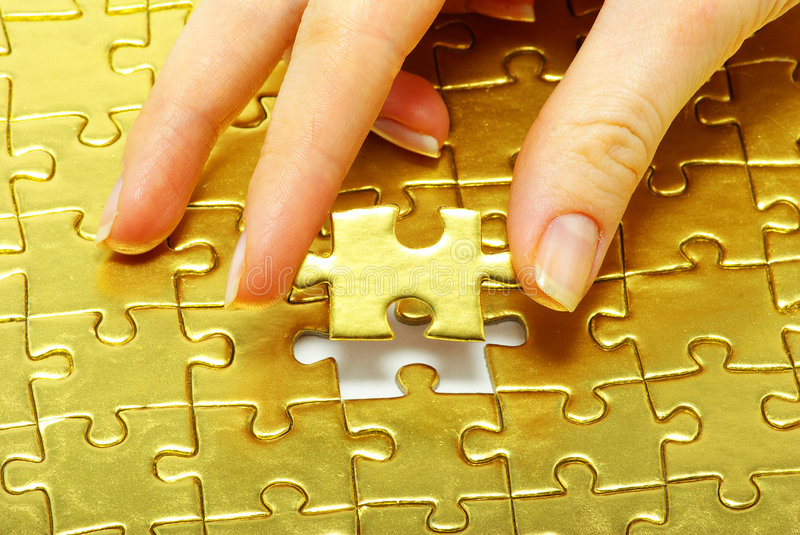 Gold pazles. Woman fingers holdings gold pazles stock image