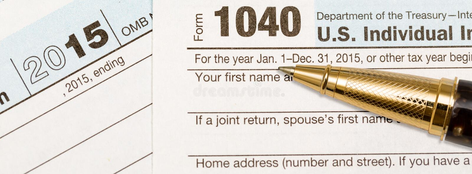 Gold pen laying on 2015 IRS form 1040. USA IRS tax form 1040 for year 2015 with gold ballpoint pen, Suitable for header image for tax preparer or accountant stock images