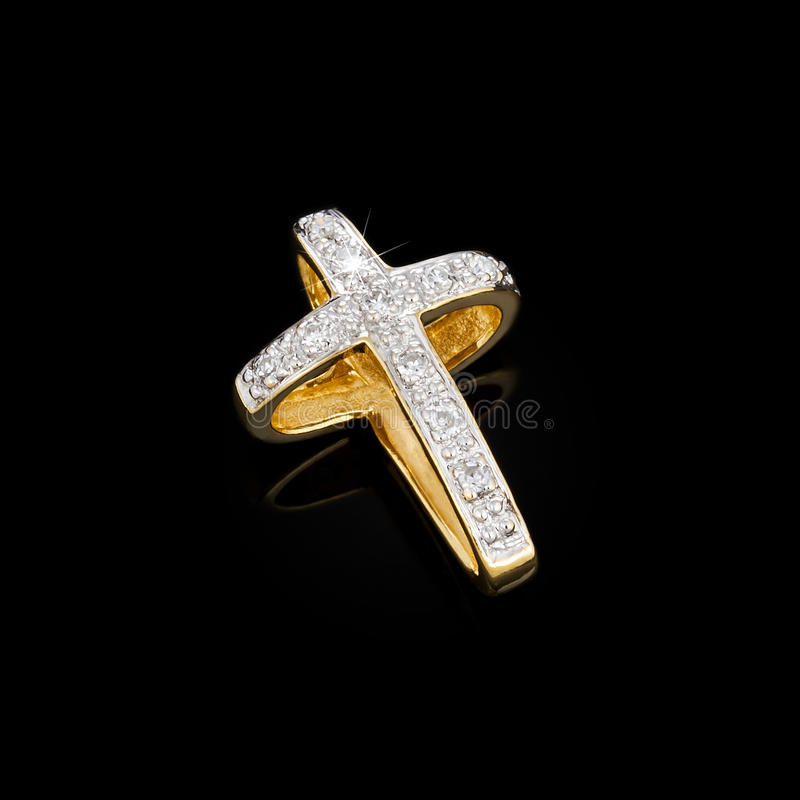 Gold pendant in the shape of a cross stock photos