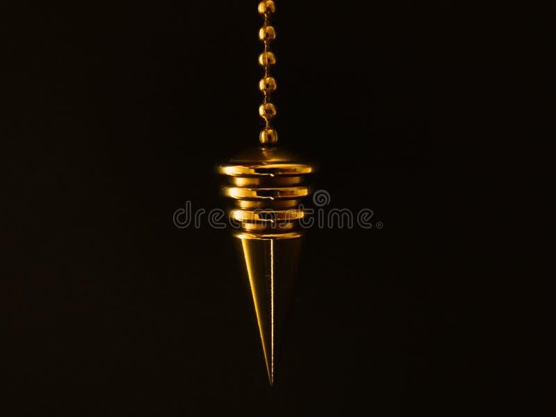 Gold pendulum royalty free stock photography