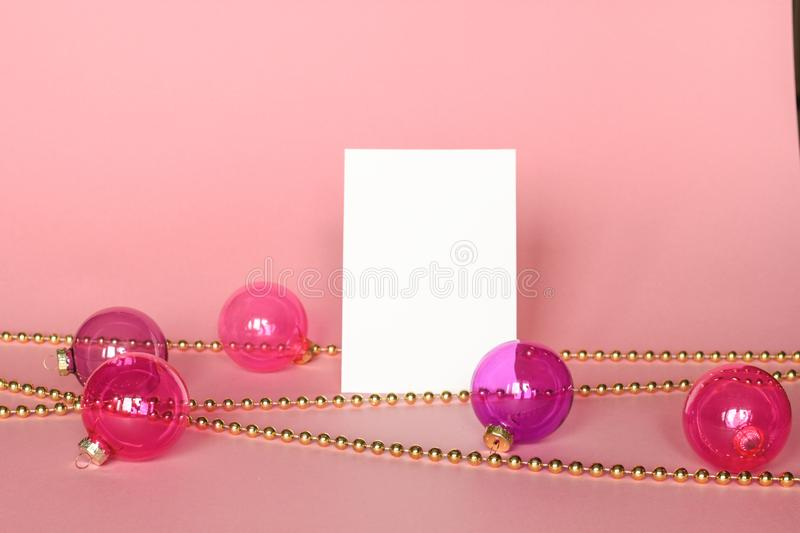 Gold picture frame with christmas ornaments. Mockup on pink background. Fashion decoration stock image