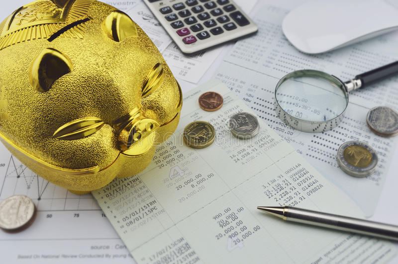 Gold piggy bank with coin on saving account book. Saving concept stock images