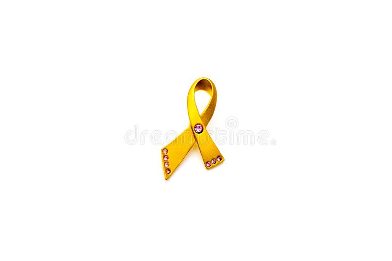 Gold and pink breast cancer awareness pin isolated on white background; women`s healthcare concept. Breast care concept. Closeup gold breast cancer pin with pink royalty free stock photo