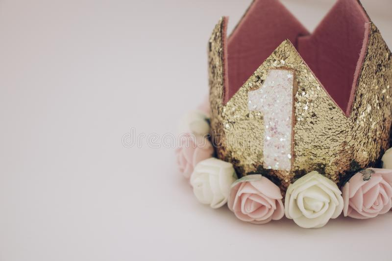 Gold and pink first birthday crown on pink background stock photos