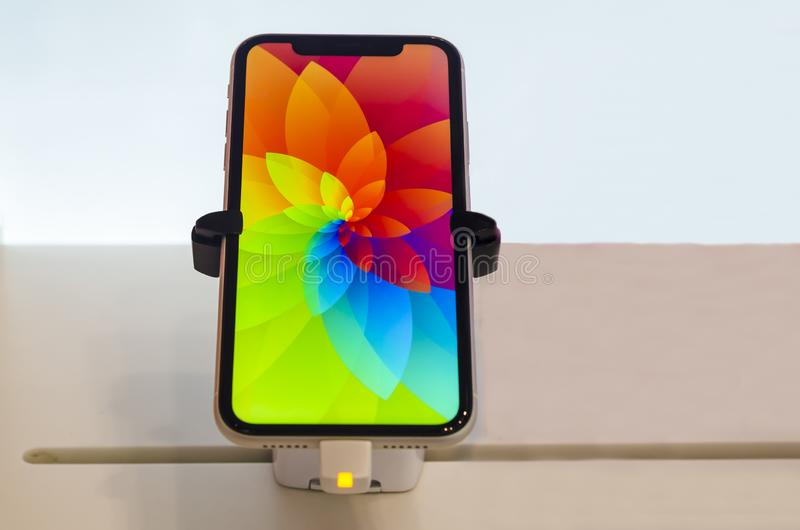 Gold, pink iPhone XR smartphone goes on sale in Apple Store Computers with screensaver on Liquid Retina display LCD. Saint-Petersburg, Russia - December 3, 2019 royalty free stock photo