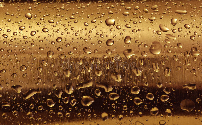Gold plate with water drops on the rounded surface. stock image