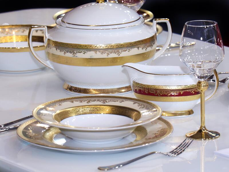 Gold plates table set. Retro table set with gold plates and bowl stock image