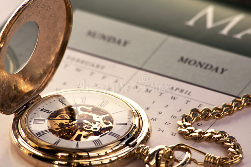 Gold pocket watch and calendar royalty free stock images