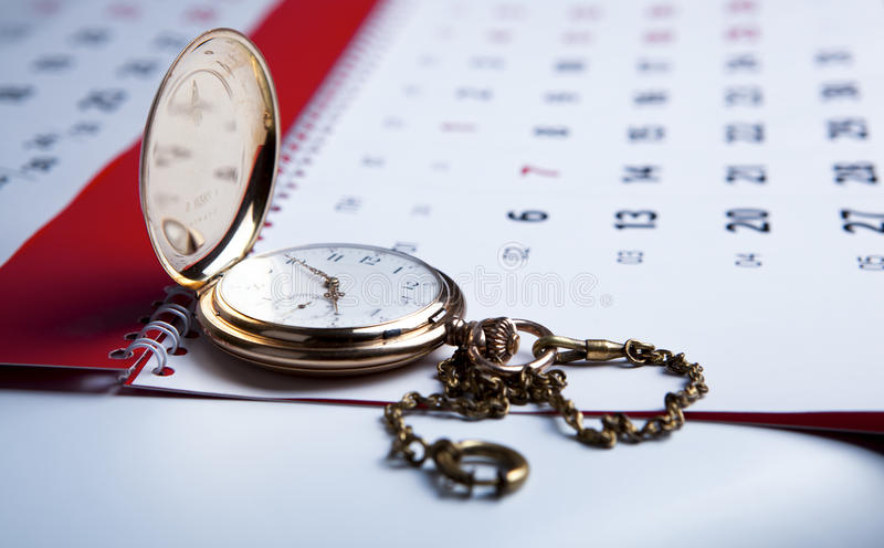 Gold pocket watch and a wall calendar stock image