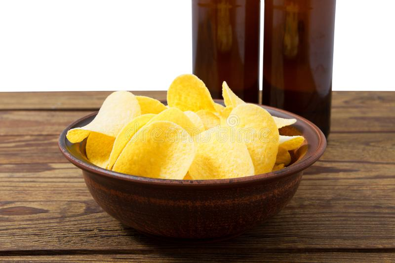 Gold potato chips on grey plate on wood table isolated on white background stock photography