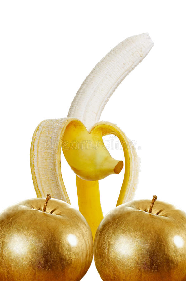 Gold power. One ripe banana on white surface with two gold apples royalty free stock photography