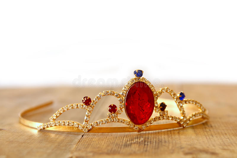 Gold princes crown on wooden table. selective focus. Image of gold princes crown on wooden table. selective focus stock images