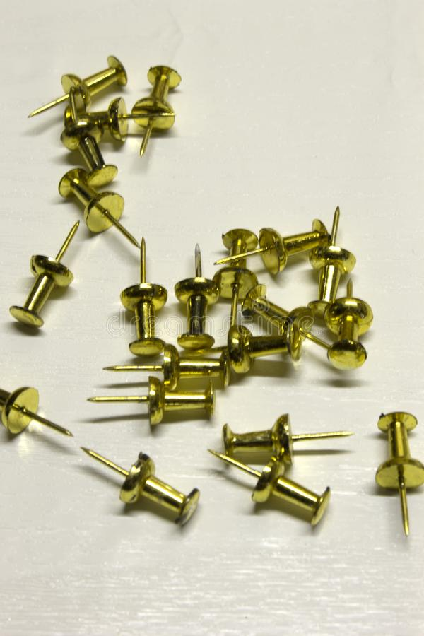 Gold Push pins. Isolated on a textured White background royalty free stock photography