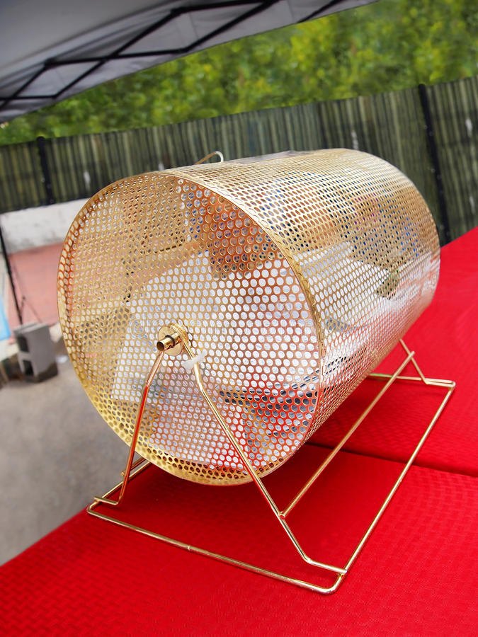 Gold Raffle Drum. A traditional gold raffle drum full of contest entry ballots on a table top at an outdoor event stock image