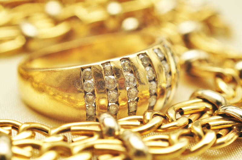 Gold ring macro. Macro of gold ring with stones and gold chain royalty free stock image