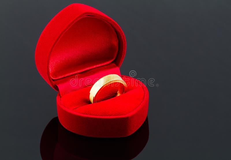 Gold ring in red heart shaped velvet box on dark glossy backgro stock image