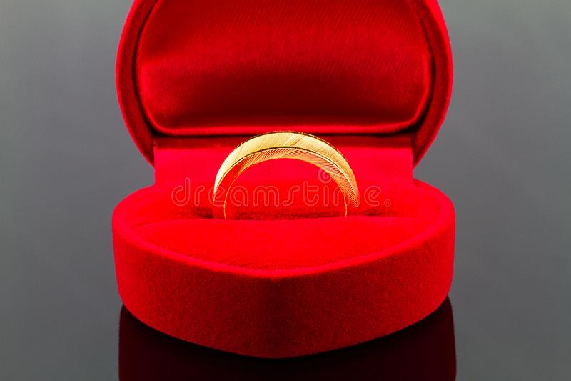 Gold ring in red heart shaped velvet box on dark glossy backgro stock images