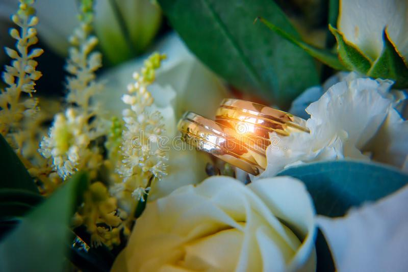 Gold rings on a bridal bouquet, close-up. Shiny wedding rings among white flowers in bright light.  stock photography