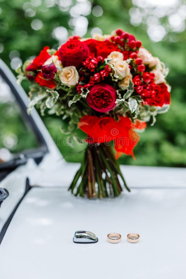 Gold rings lying on white car in background of passion wedding bouquet with dark red and marsala roses, greenery. Bridal flowers, royalty free stock image