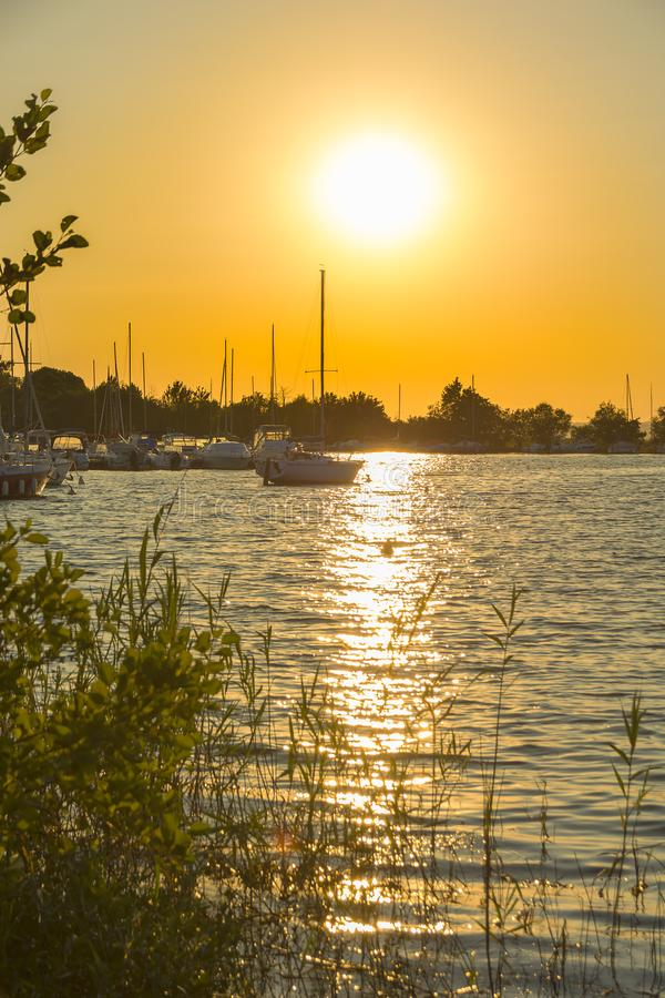 Gold romantic sunset over lake with silhouettes of yachts stock photography