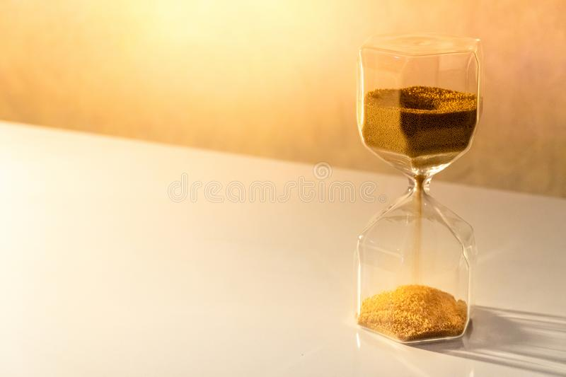 Hourglass on white table, Time passing concept. Gold sand running through the shape of modern hourglass on white table.Time passing and running out of time royalty free stock photos