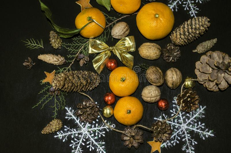 Gold satin bow and tangerines with a sprig of cypress, cones,nuts,chocolate with snowflakes on a black plywood stock photos