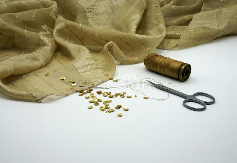 Gold sequins, spool of golden thread, needle on rippled gold silk background. Sewing and decorating accessories used for stock photo