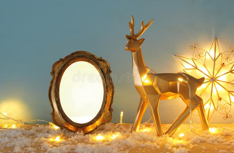 Gold shiny reindeer and empty photo frame on snowy wooden table with christmas garland lights. For photography and scrapbook monta royalty free stock images