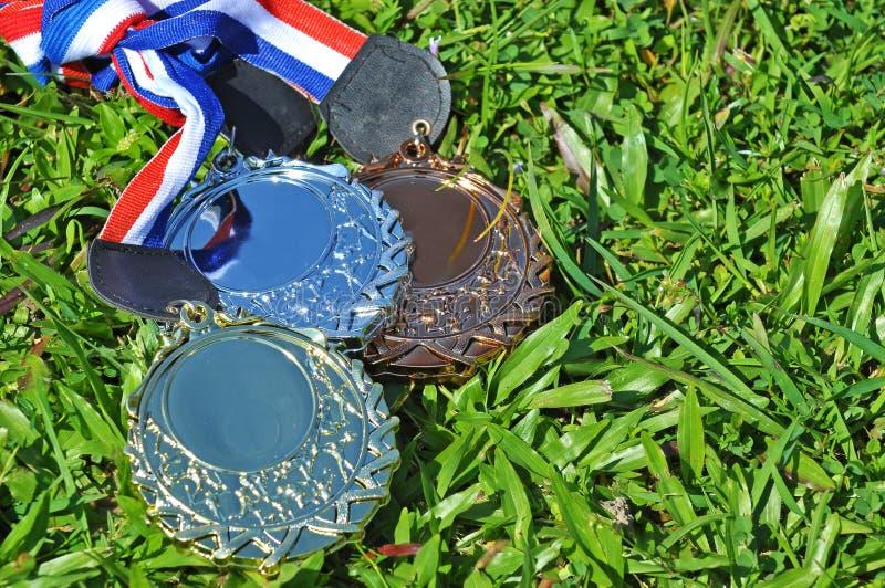 Gold-, silberne und Bronzemedaille auf dem grünen Gras lizenzfreies stockbild