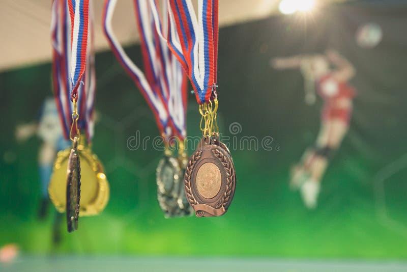 Gold-, silberne und Bronzemedaille auf Hintergrund des Plakats mit Volleyballspielern stockbild