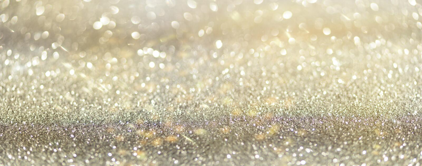 Gold and silver abstract bokeh lights. Shiny glitter background with copy space. New year and Christmas concept. Sparkling royalty free stock image