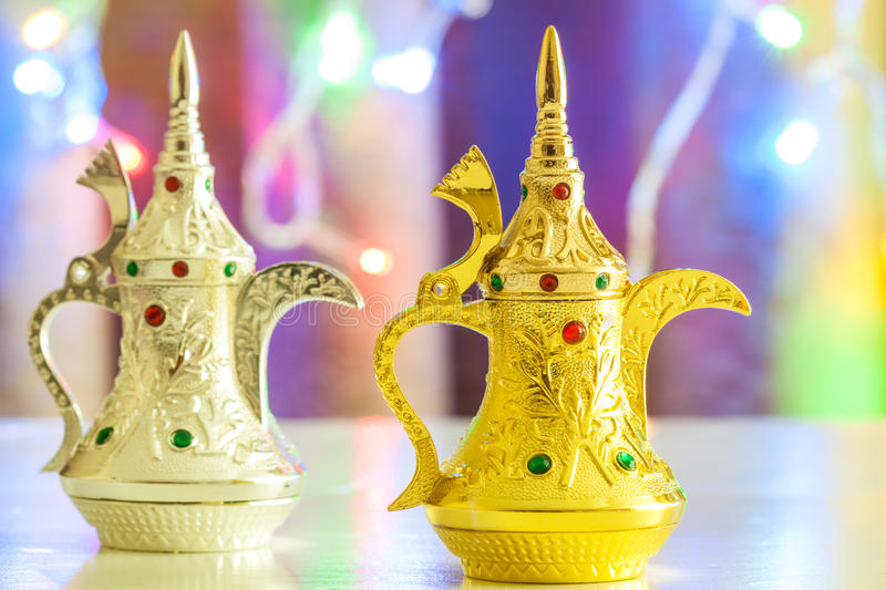 Gold and Silver Arabic Coffee pots in colorful illuminated background. Ramadan and Eid concept background stock photos