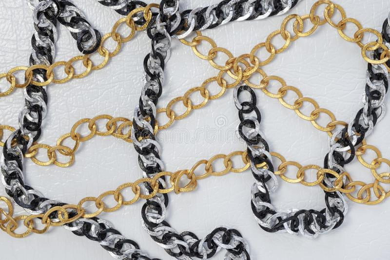 Gold, silver and black colors chains on white leather background royalty free stock image