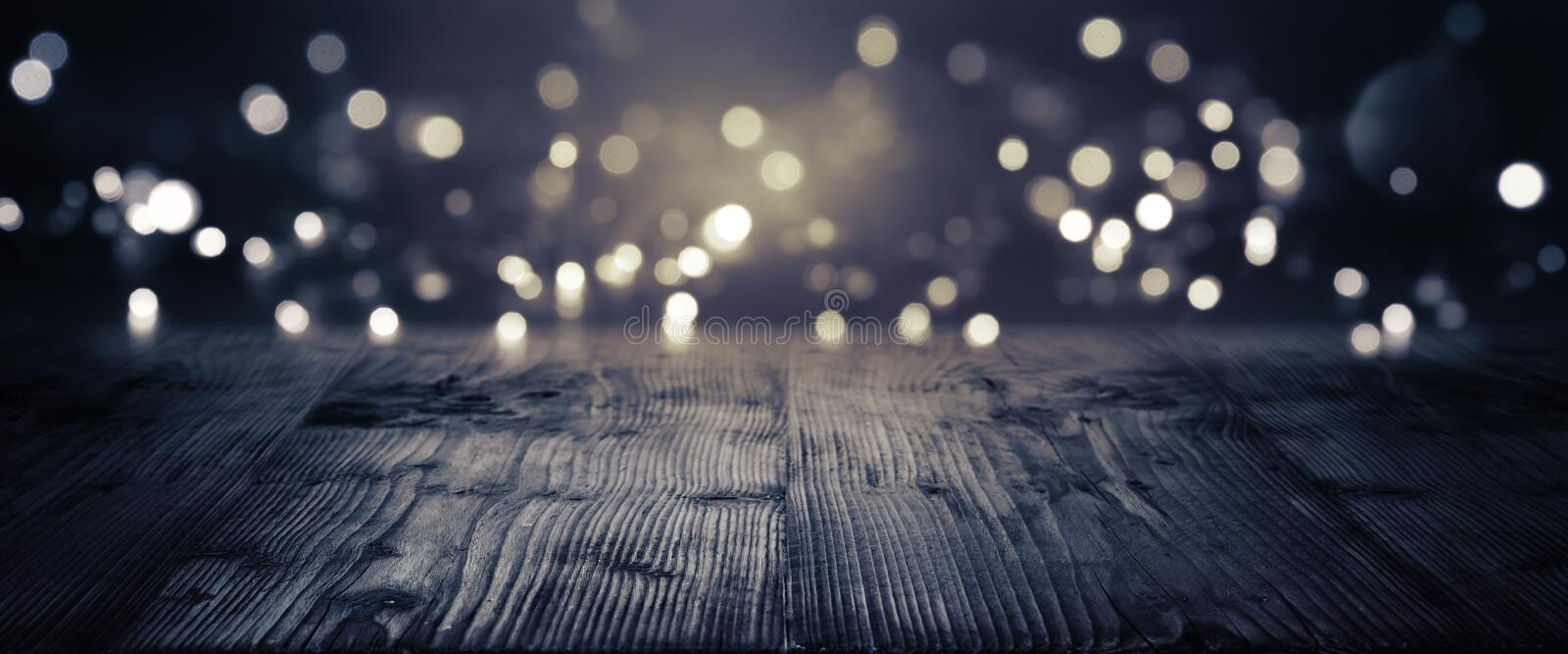 Gold and silver bokeh on a dark background. With empty wooden floor for a festive concept stock image