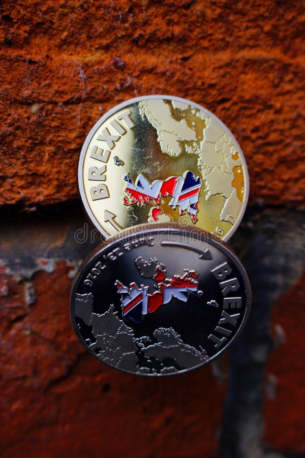 Gold and silver brexit. Two coins. Gold and silver brexit money with british map on brick wall stock photo