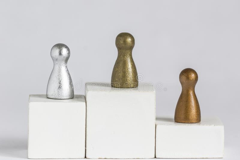Gold, Silver and Bronze gamefigurine on a winner podium royalty free stock photography