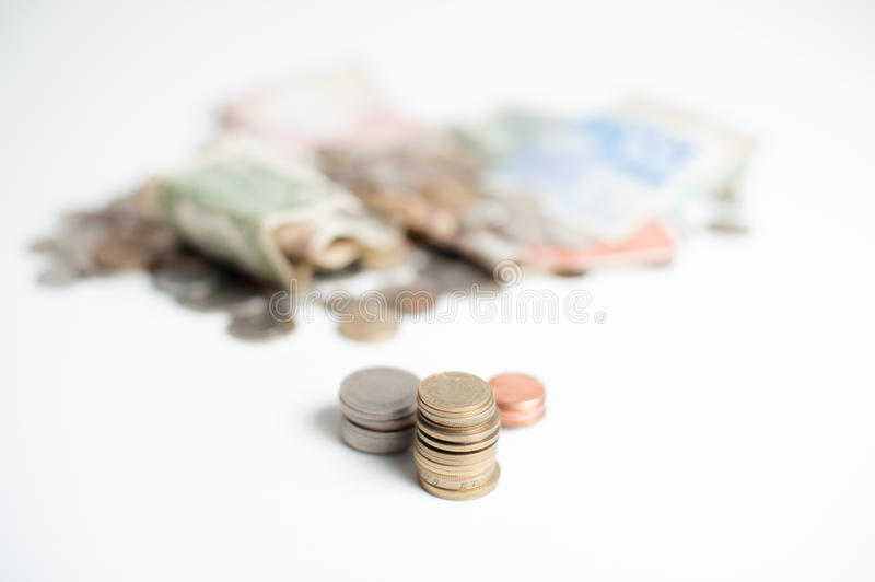 Gold, silver, and bronze piles of coins. Three piles of coins, gold, silver, and bronze, with mountain of money coins and banknotes out of focus in background royalty free stock images