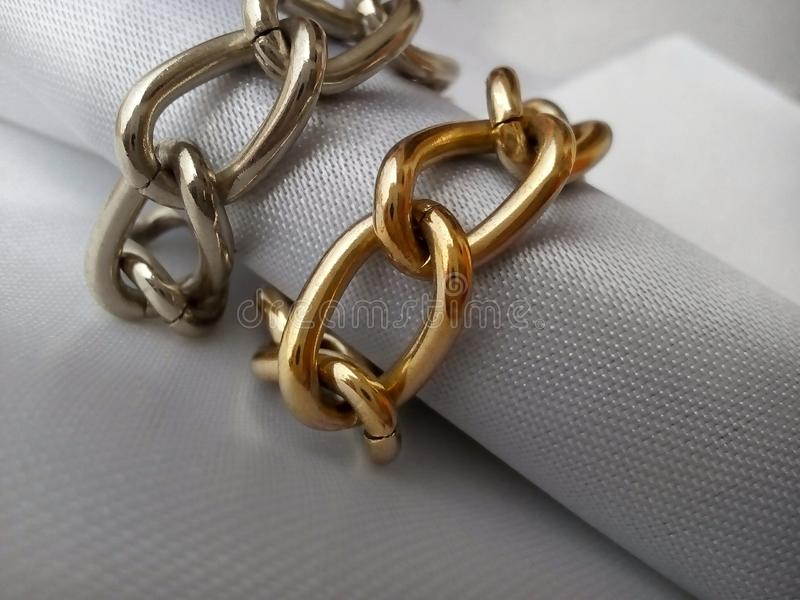 Gold and silver chain wrapped around a white textured fabric roll stock photo