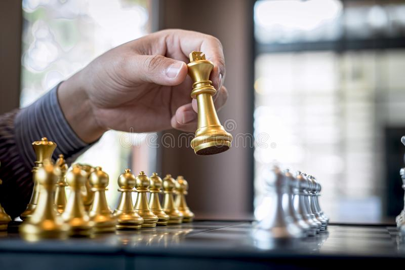 Gold and silver chess with player, Intelligent businessman playing chess game competition to planning business strategic to. Development for win and success stock photo