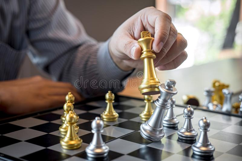 Gold and silver chess with player, Intelligent businessman playing chess game competition to planning business strategic to. Development for win and success royalty free stock image