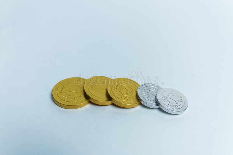 Gold and silver chocolate coins in wrappers stock image