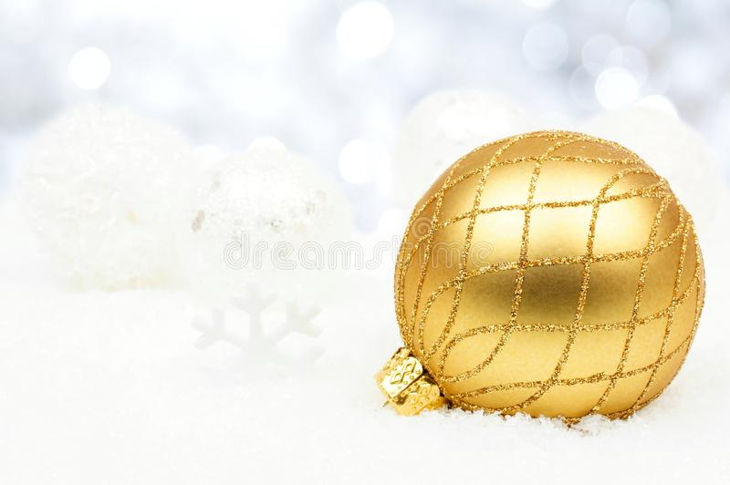 Gold and silver Christmas ornaments in snow with twinkling background. Gold and silver Christmas ornaments resting in fresh winter snow with twinkling background stock image