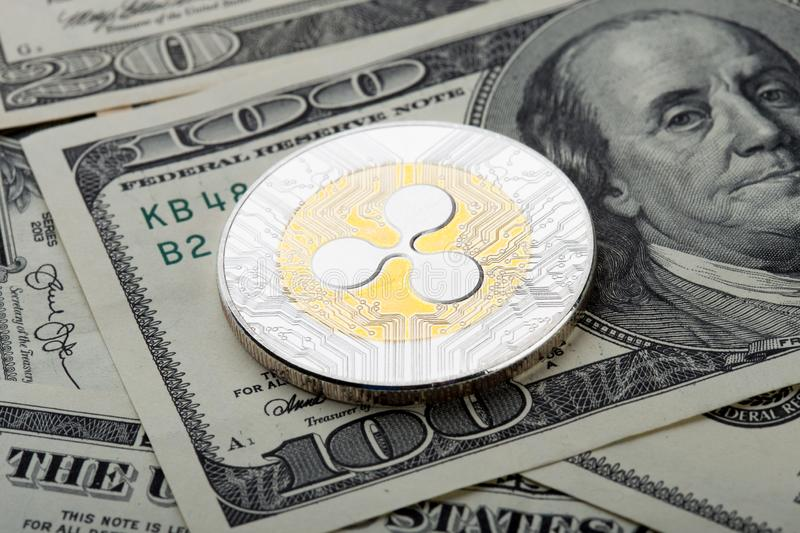 Gold and silver coin - Ripple crypto currency. Virtual currency on the hundred dollar bill. Cash, digital, electronic, money, net, pay, payment, banking, bills stock photography